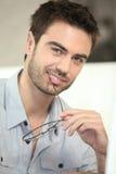 Mann, der seine Gläser beißt Stockfoto