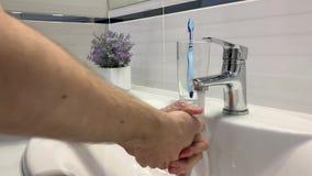 Mann, der seine Hände unter dem Hahn im Badezimmer wäscht stock footage