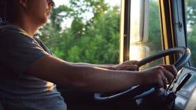 Mann, der seine Hand auf dem Lenkrad hält und einen LKW an der Landstraße am sonnigen Sommertag fährt Progile des Kaukasiers stock video