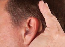 Mann, der seine Hand hinter seinem Ohr höhlt Stockfoto