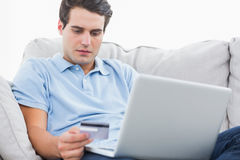 Mann, der seine Kreditkarte verwendet, um online zu kaufen stockfotografie