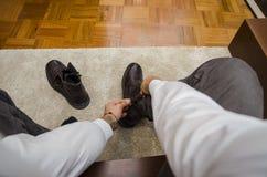 Mann, der seine Schnürsenkel binden ankleidet lizenzfreies stockfoto