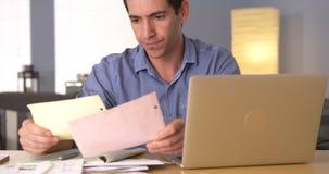 Mann, der seine Steuern am Schreibtisch tut Stockbilder