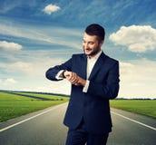 Mann, der seine Uhr über Straße betrachtet Lizenzfreie Stockfotografie