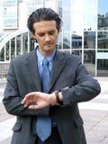 Mann, der seine Uhr betrachtet stockbild
