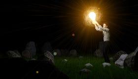 Mann, der seine Weise mit Glühlampe beleuchtet Stockbilder