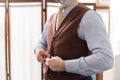 Mann, der seine Weste knöpfend ankleidet lizenzfreie stockbilder