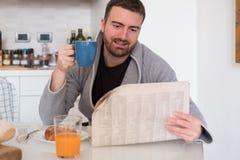 Mann, der seine Zeitung während des Morgenfrühstücks liest Lizenzfreies Stockfoto