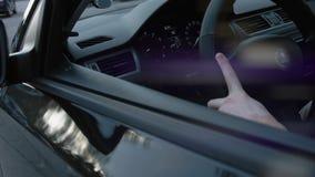 Mann, der in seinem Auto, Hand auf dem Lenkrad, die Kamera betrachtend durch den Seitenspiegel sitzt Langsame Bewegung stock video footage