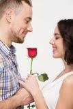 Mann, der seinem eine Rose geliebt gibt Stockfotografie