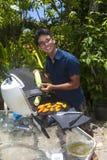 Mann, der in seinem Garten grillt lizenzfreie stockfotografie