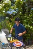 Mann, der in seinem Garten grillt Stockfotos