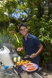 Mann, der in seinem Garten grillt Lizenzfreies Stockbild