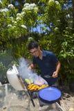 Mann, der in seinem Garten grillt Lizenzfreies Stockfoto