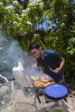 Mann, der in seinem Garten grillt Lizenzfreie Stockfotos