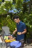 Mann, der in seinem Garten grillt stockfotografie