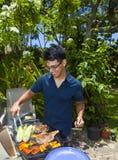 Mann, der in seinem Garten grillt lizenzfreie stockbilder