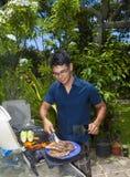 Mann, der in seinem Garten grillt stockfoto