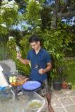Mann, der in seinem Garten grillt stockbild