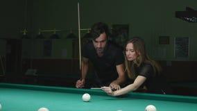 Mann, der seinem Mädchen zeigt, wo man den Ball - junge Frau schlägt, die Rat auf Schießen-Pool-Ball beim Spielen von Billard emp stock video
