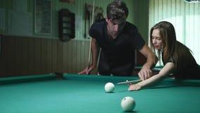 Mann, der seinem Mädchen zeigt, wo man den Ball - junge Frau schlägt, die Rat auf Schießen-Pool-Ball beim Spielen von Billard emp stock footage