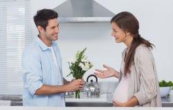 Mann, der seinem schwangeren Partner Blumen gibt Stockfoto