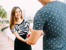 Mann, der seinem weiblichen Partner eine Geschenkbox gibt Glückliches Verhältnis Szene in der im Freien Liebes- und Verhältnis-Ko Lizenzfreies Stockbild