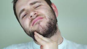 Mann, der seinen Bart verkratzt stock footage