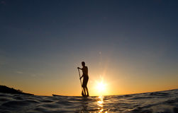 Mann, der seinen Brandungvorstand am Sonnenuntergang schaufelt Lizenzfreies Stockfoto