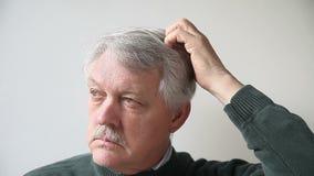 Mann, der seinen Kopf verkratzt stock video