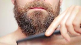 Mann, der seinen Schnurrbart und Bart kämmt stock footage