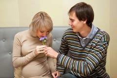 Mann, der seinen schwangeren Fraublumenstrauß gibt Lizenzfreie Stockbilder