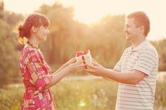 Mann, der seiner Frau eine Geschenkbox gibt. Retrostil. Lizenzfreies Stockbild