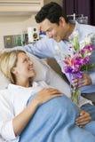 Mann, der seiner schwangeren Frau Blumen gibt Stockfotografie