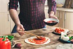 Mann, der selbst gemachte Pizza auf einem Holztisch kocht Stockbilder