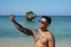 Mann, der selfie auf Strand nimmt stockfotos
