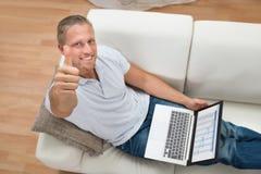 Mann, der sich Daumen beim Arbeiten an Laptop zeigt Lizenzfreies Stockfoto