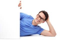 Mann, der sich mit leerem Plakat hinlegt Lizenzfreies Stockbild
