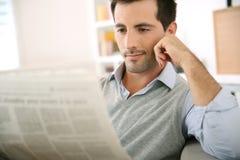 Mann, der sich zu Hause mit Zeitung in den Händen entspannt Stockfotos