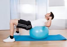 Mann, der Sit Ups On Fitness Ball tut Stockfoto