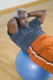 Mann, der Sitzen-UPS auf einem Pilates-Ball tut Stockfotografie