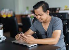 Mann, der Smartphone in einem Café verwendet Lizenzfreie Stockfotografie