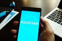 Mann, der Smartphone mit Blockchain hält Lizenzfreie Stockfotos