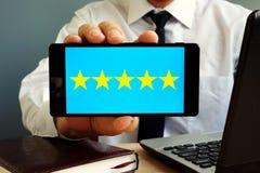 Mann, der Smartphone mit dem Veranschlagen mit fünf Sternen hält Kundendienst Lizenzfreie Stockfotos