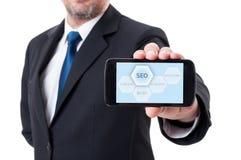 Mann, der Smartphone mit SEO-Diagramm hält Stockfotos