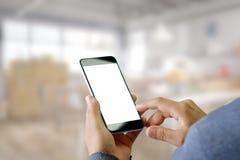 Mann, der Smartphone mit unscharfem Bürohintergrund verwendet Stockfotografie