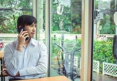 Mann, der Smartphone neben Fenster schaut lizenzfreies stockbild