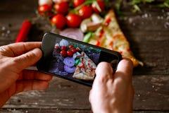 Mann, der Smartphone verwendet, um Foto der Scheibe der Pizza zu machen Stockbilder