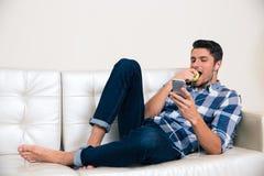 Mann, der Smartphone verwendet und Apfel isst Stockbilder