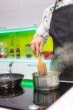 Mann, der Soße kocht Stockfotos